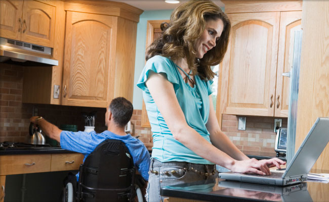 Woman with laptop with male in wheelchair in kitchen