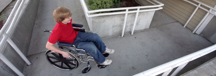 Child in wheelchair using ramp